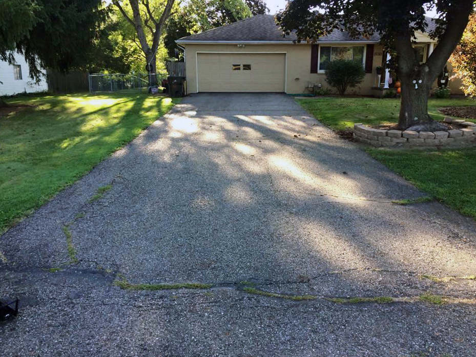 Old and weather asphalt driveway in need of a replacement.
